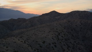 AX0012_066 - 5K stock footage aerial video fly low over desert mountains, Mojave Desert, California, sunset