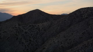 AX0012_067 - 5K stock footage aerial video of approaching a desert mountain, Mojave Desert, California