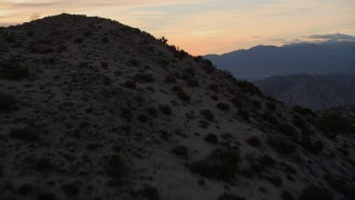 AX0012_068 - 5K stock footage aerial video fly over desert mountain revealing a valley, Mojave Desert, California, sunset