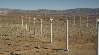 AX0013_014E - 5K stock footage aerial video of flying by windmills in the desert, San Gorgonio Pass Wind Farm, California