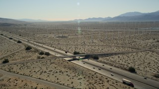 AX0013_019 - 5K stock footage aerial video of interstate cutting through desert wind farm, San Gorgonio Pass Wind Farm, California