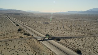 AX0013_024 - 5K stock footage aerial video of flying over an interstate passing through desert and a windmill farm, Palm Springs, California