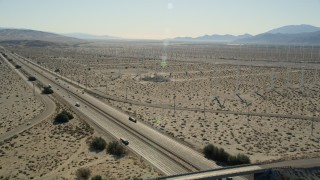 AX0013_025 - 5K stock footage aerial video fly over interstate toward windmills, San Gorgonio Pass Wind Farm, California