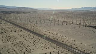 AX0013_026E - 5K stock footage aerial video fly over windmills, orbit railroad tracks, San Gorgonio Pass Wind Farm, California