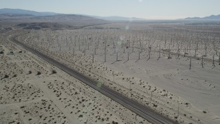 AX0013_027 - 5K stock footage aerial video of orbiting train tracks trough a windmill farm, San Gorgonio Pass Wind Farm, California