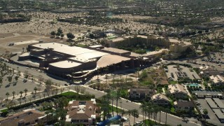 AX0013_037E - 5K stock footage aerial video of fly over residential neighborhoods toward a convention center, West Palm Springs, California