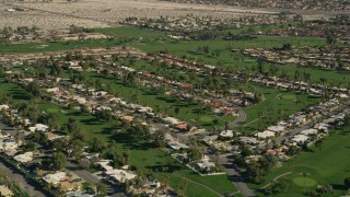 AX0013_053E - 5K aerial stock footage video of residential neighborhoods and golf course, West Palm Springs, California