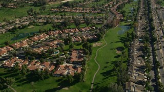 AX0013_070 - 5K stock footage aerial video of condominiums surrounded by a golf course, Palm Desert, California