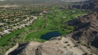 AX0013_077 - 5K stock footage aerial video of a golf course bordered by mountains, Indian Wells, California