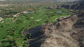 AX0013_078 - 5K stock footage aerial video fly by a golf course at the base of a mountain, Indian Wells, California