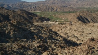 AX0013_081 - 5K stock footage aerial video fly over mountain toward a valley community, Indian Wells, California