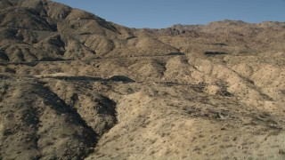 AX0014_002 - 5K stock footage aerial video approach a mountain peak revealing a highway, San Jacinto Mountains, California