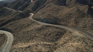 AX0014_003 - 5K stock footage aerial video approach a highway through San Jacinto Mountains, California