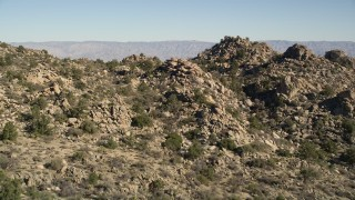 AX0014_009 - 5K stock footage aerial video fly over stony mountains revealing Caochella Valley, San Jacinto Mountains, California
