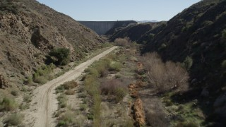 AX0014_029 - 5K stock footage aerial video of following a dirt Road leading to Hemet Dam, California