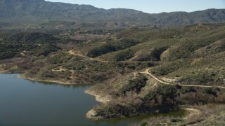 AX0014_032 - 5K stock footage aerial video fly over lake shore toward a country road in the hills, Lake Hemet, California
