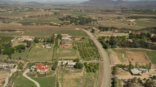 AX0014_056 - 5K stock footage aerial video fly over rural homes and vineyards, Temecula, California