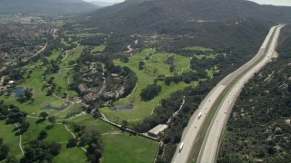 AX0015_001 - 5K stock footage aerial video follow Interstate by golf course and hills, Temecula, California