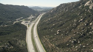 AX0015_003 - 5K stock footage aerial video of interstate at the foot of mountains, Temecula, California