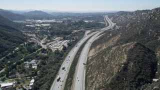 AX0015_006 - 5K stock footage aerial video follow light traffic on an interstate through hills, Temecula, California
