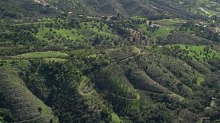 AX0015_015 - 5K stock footage aerial video of flying over hills toward farmland, Fallbrook, California