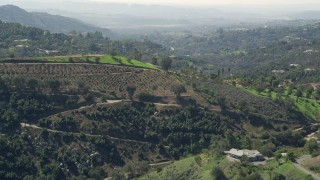 AX0015_019 - 5K stock footage aerial video approach farmland and homes on hills, Fallbrook, California
