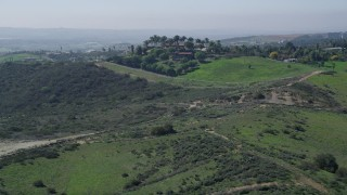AX0015_028 - 5K stock footage aerial video approach a large house atop a hill, Fallbrook, California