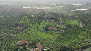 AX0015_035 - 5K stock footage aerial video of large homes and farmland atop a hill, Fallbrook, California