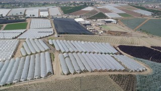 AX0015_036 - 5K stock footage aerial video fly over farmland and greenhouses, Fallbrook, California