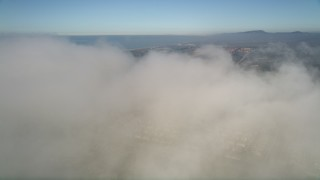 AX0015_055E - 5K stock footage aerial video fly over a dense cover of clouds below blue skies, reveal tract homes in Oceanside, California