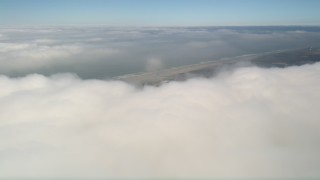 AX0016_014 - 5K stock footage aerial video tilt from dense cloud layer to reveal the coastline, Camp Pendleton, California