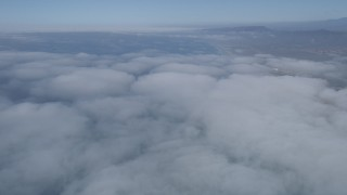 AX0016_019 - 5K stock footage aerial video fly over clouds breaking up over the coast near Camp Pendleton, California