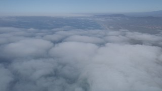 AX0016_020 - 5K stock footage aerial video fly above clouds breaking up over the coast, Camp Pendleton, California