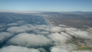 AX0016_021 - 5K stock footage aerial video fly over clouds breaking up along the coast, Camp Pendleton, California