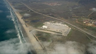 AX0016_023 - 5K stock footage aerial video approach and tilt to Camp Pendleton by the coast, seen through the clouds, California