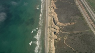 AX0016_029 - 5K stock footage aerial video of a bird's eye view of coastal cliffs and empty beach in Oceanside, California