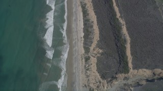 AX0016_031 - 5K stock footage aerial video of a bird's eye view of waves rolling toward beach and coastal cliffs, Oceanside, California