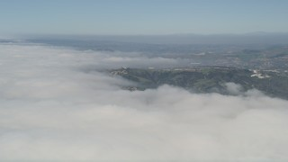 AX0016_037 - 5K stock footage aerial video fly over clouds to approach a group of hillside homes, San Clemente, California