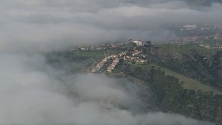 AX0016_038 - 5K stock footage aerial video approach hillside suburban homes bordered by clouds, San Clemente, California