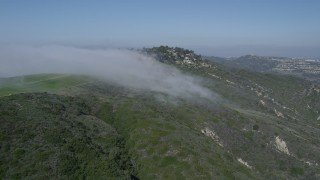 AX0016_057 - 5K stock footage aerial video of flying by fog rolling over a hill to approach upscale, hillside neighborhood, Laguna Niguel, California
