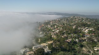 AX0016_058 - 5K stock footage aerial video fly over upscale hillside homes and rolling fog, Laguna Niguel, California