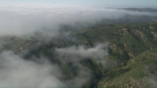 AX0016_062 - 5K stock footage aerial video approach a dirt road atop hills near the edge of rolling fog, Laguna Beach, California