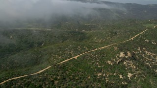AX0016_063 - 5K stock footage aerial video fly over and pan across a dirt road on a hill near rolling fog, Laguna Beach, California