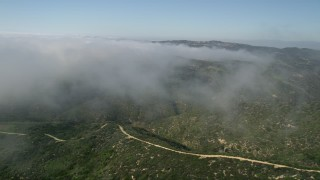 AX0016_064 - 5K stock footage aerial video fly over green hills and rolling fog, Laguna Beach, California