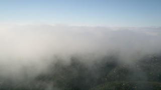 AX0016_065 - 5K stock footage aerial video of flying by the edge of a cloud bank, Laguna Beach, California