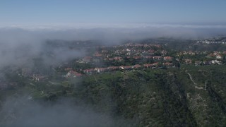 AX0016_070 - 5K stock footage aerial video approach and fly over hilltop mansions near a fog bank, Newport Beach, California