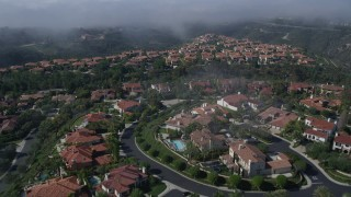 AX0016_071 - 5K stock footage aerial video fly over large, upscale homes to approach a fog bank, Newport Beach, California