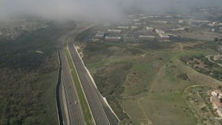 AX0016_077 - 5K stock footage aerial video flyby light traffic on Highway 73 near homes and office buildings Irvine, California