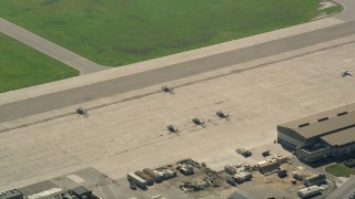 AX0016_099 - 5K stock footage aerial video flyby parked military helicopters at Los Alamitos Army Airfield, California
