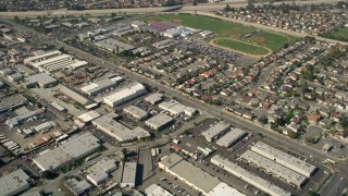 AX0016_101 - 5K stock footage aerial video tilt from warehouses to reveal Los Alamitos High School, residential neighborhoods, and Coyote Creek, Los Alamitos, California